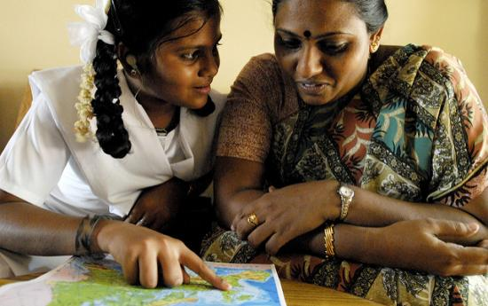 Indian girl looking at map with mother
