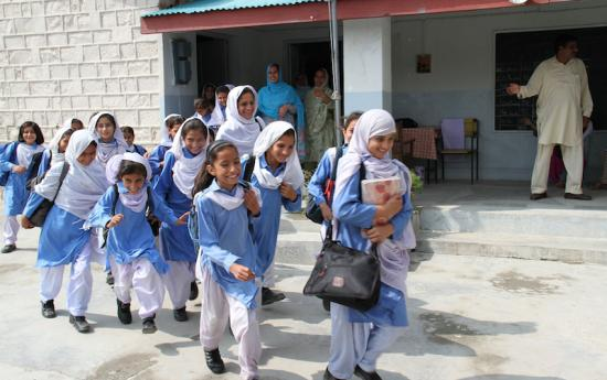 Smiling schoolgirls walking together