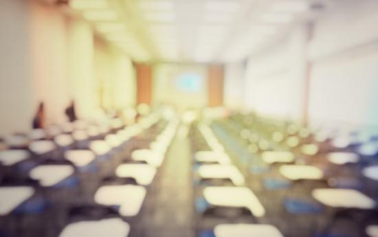 Blurred image of classroom with empty desks