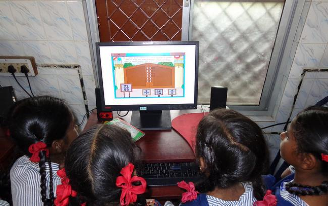 Four schoolgirls looking at a computer screen