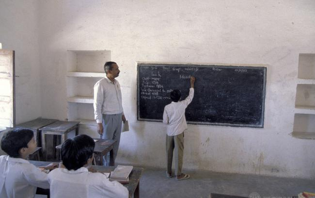 Student at blackboard in India with teacher watching