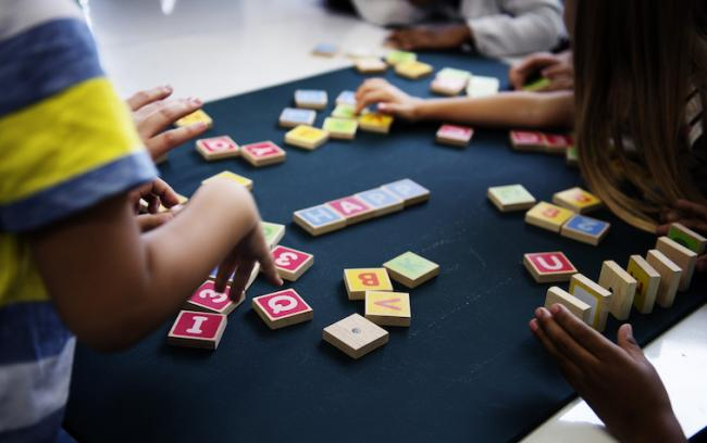 Students' hands playing with wooden letter blocks