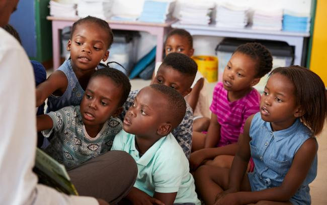 Children in a classroom listening to a teacher