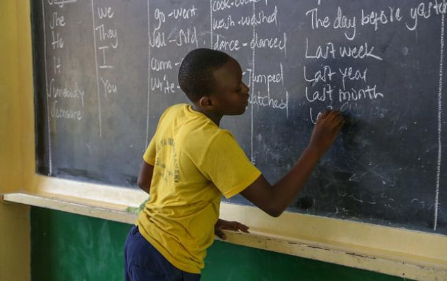 Schoolboy at chalkboard in classroom