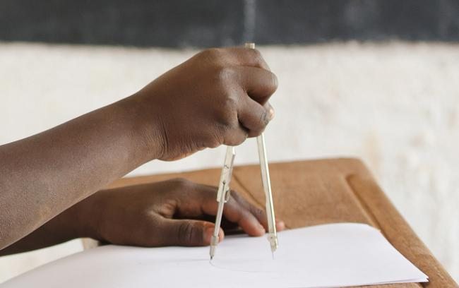 A student's hands as she uses a pair of compasses in a classroom (353)