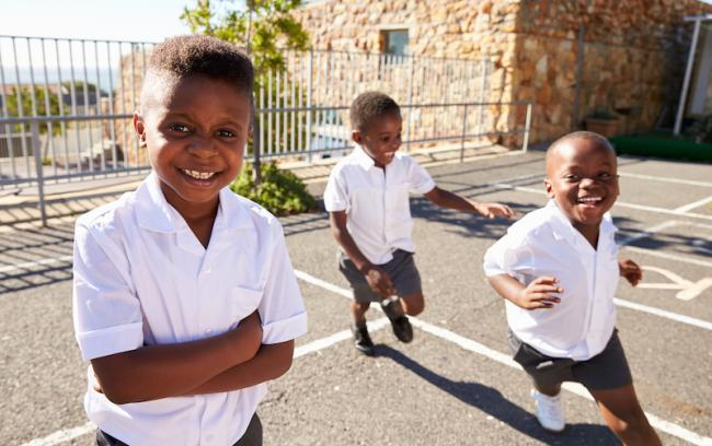 Three schoolboys running and smiling